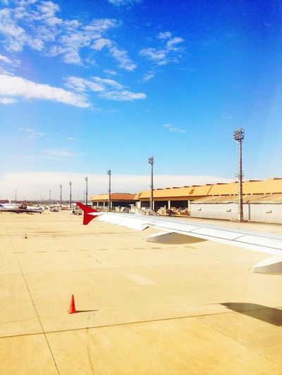 Commercial Airplanes At Airport Against Sky