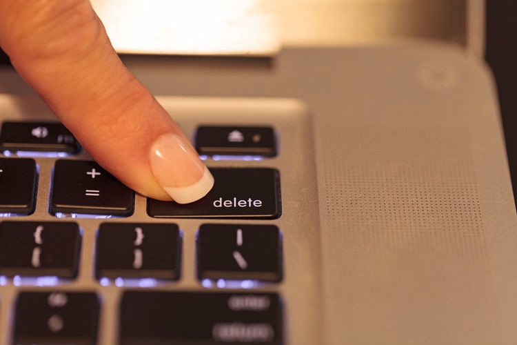 Cropped finger of woman pressing button on laptop