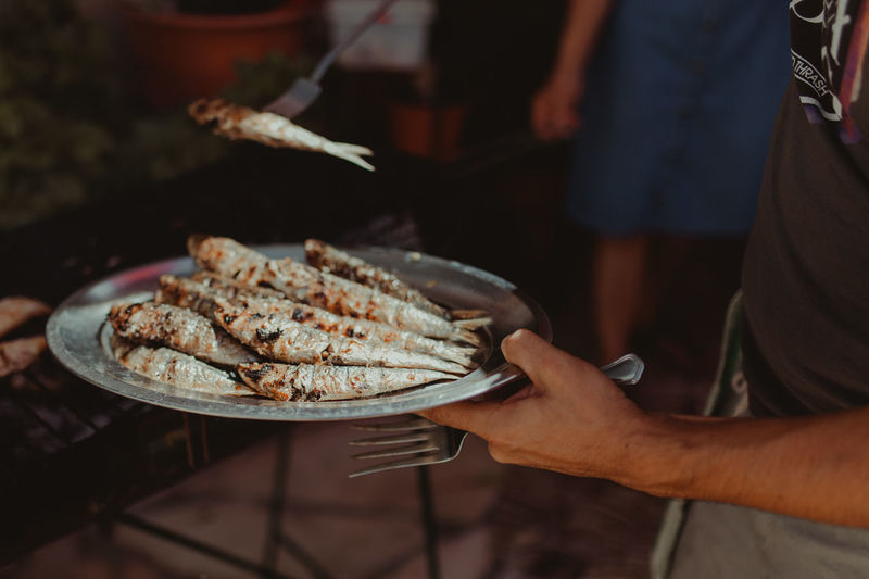 Midsection Of Man Holding Fish In Plate
