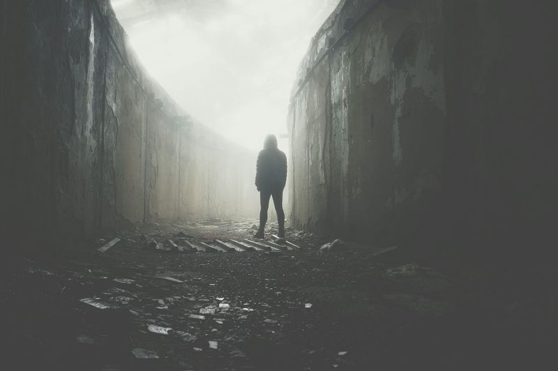 Silhouette Man Walking Amidst Wall In Foggy Weather