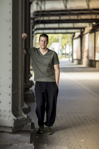 Handsome man dressed in sportswear posing for the camera in an urban street setting. Long shot. Adult Afternoon Athletic Front Facing Green Color Long Shot Man Running Shoes Standing Black Bridge Caucasian Day Daylight Handsome Lifestyles Sportwear Sporty Street Summer Sweat Pants  T-shirt Tall Urban V-neck
