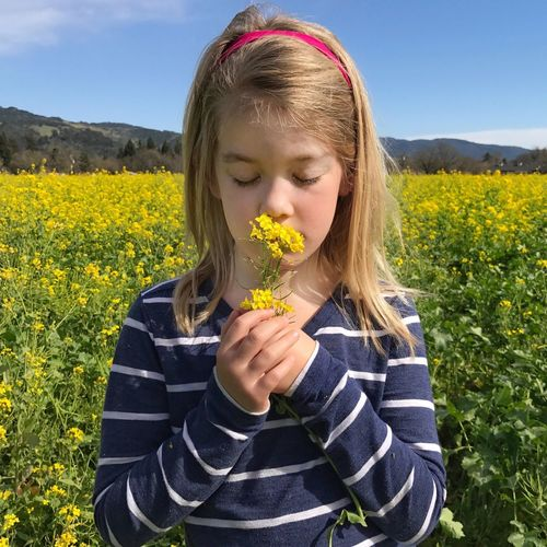 Close-up of a girl with yellow dandelion on field