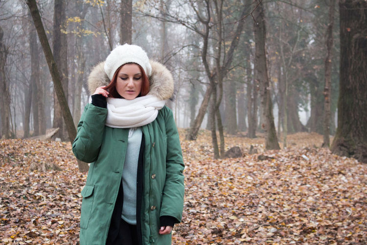 woman walking against trees during winter