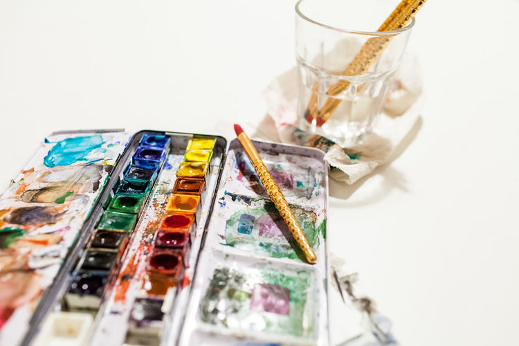 High angle view of paintbrushes on table against white background