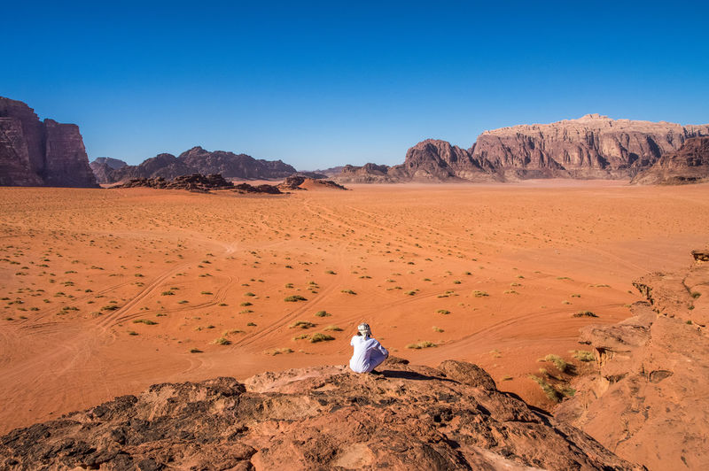 One Bedouin nomad with dessert view Adult Adults Only Beduin Clear Sky Day Desert Full Length Jordan Mountain Nature One Person Orange Outdoors People Real People Red Relaxation Sand Sand Dune Sky Solitude Wadi Rum White EyeEmNewHere The Great Outdoors - 2017 EyeEm Awards Lost In The Landscape