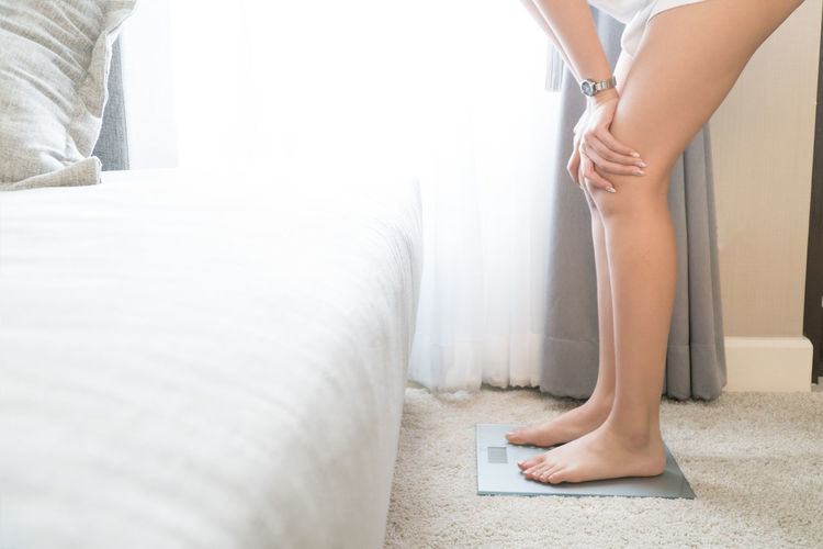Low section of woman standing on weight scale at home