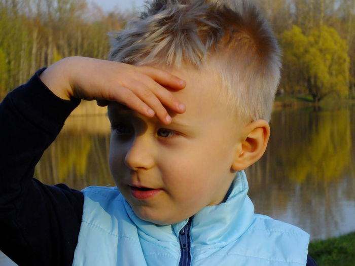 Cute boy shielding eyes against lake
