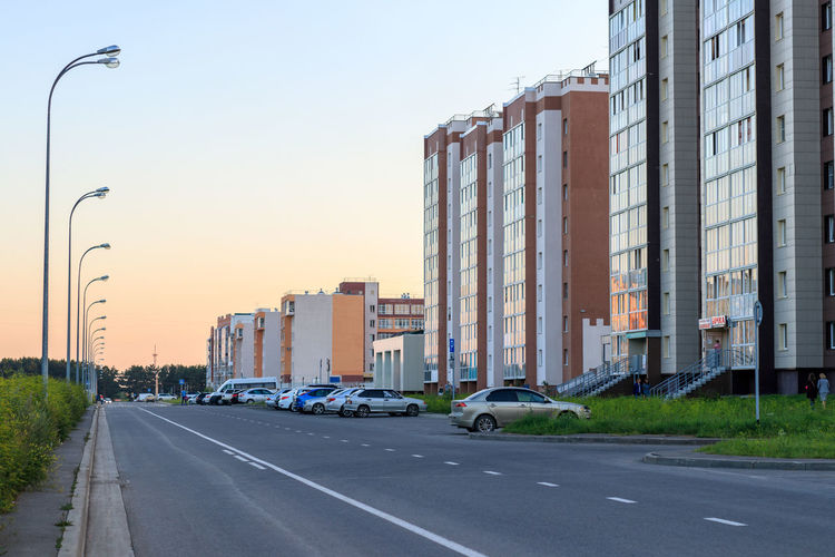 Summer evening street in Kemerovo city Sky Road Motor Vehicle Built Structure City Car Architecture Building Exterior Street Land Vehicle Road Marking Building Evening Lampposts Street Perspective