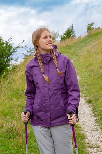 Young woman walking in the nature, Schwäbische Alb, Germany Leisure Activity Nature Women Lifestyles Hiking Walking Schwäbische Alb Outdoors Hiking Pole Healthy Eating Health Care Movement Sport Fitness Training Young Adult Girl Vertical Hohenstaufen Baden-Württemberg  Germany Happiness Smiling Jacket Rain Jacket