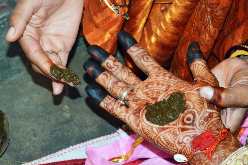 Woman put henna on groom hand to prepare indian wedding tradition called hast milap.