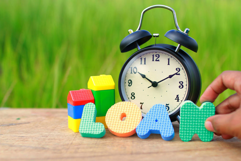Alarm clock, kid toy block and alphabet on wood with blurry green bokeh in background. Concept of banking loan. EyeEm Best Shots EyeEm Gallery EyeEmNewHere EyeEm Selects Banking Rate Loan  Human Body Part Human Hand One Person Childhood Time Indoors  Day