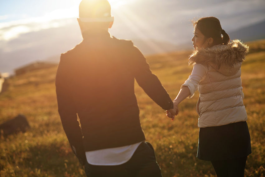 Couple holding hands outdoor with sun flare in the background Two People Togetherness Sunlight Women Three Quarter Length Bonding Emotion Leisure Activity Nature Sunset Positive Emotion Adult Standing Men Real People Field Love Lifestyles Females Lens Flare Outdoors Couple - Relationship Iceland Holding Hands Sun Flare Capture Tomorrow Human Connection