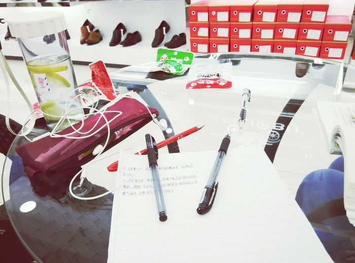 High Angle View Of Pens And Paper On Glass Table In Shoe Shop