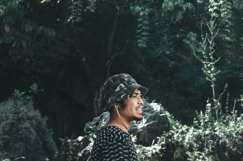 Side view of man wearing bucket hat against trees
