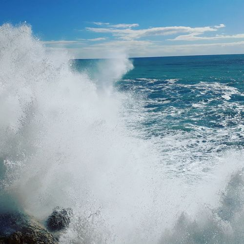 Scenic view of sea waves splashing against sky