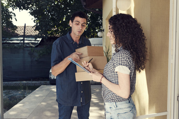 Woman signing on digital tablet while delivery man pointing against house