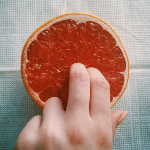 Close-up of hand holding grapefruit