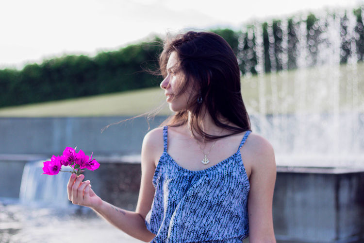 Beautiful Young Woman Holding Purple Flowers