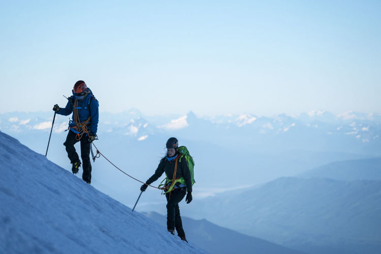 Full length of man and woman on mountain against sky