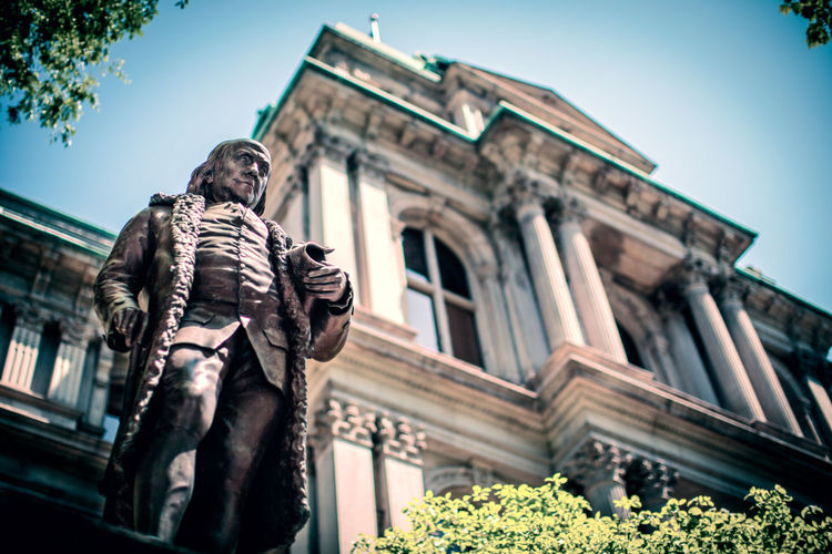 Low angle view of male statue at historic building