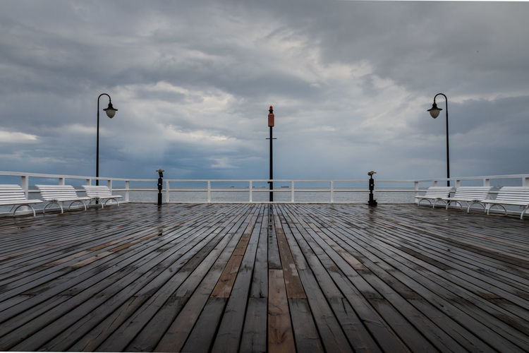 Empty pier on sea against sky