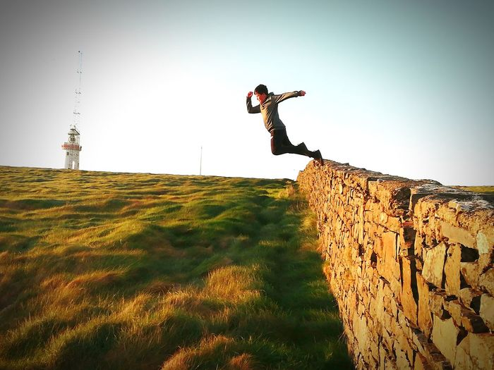 Full length of man jumping from stone wall