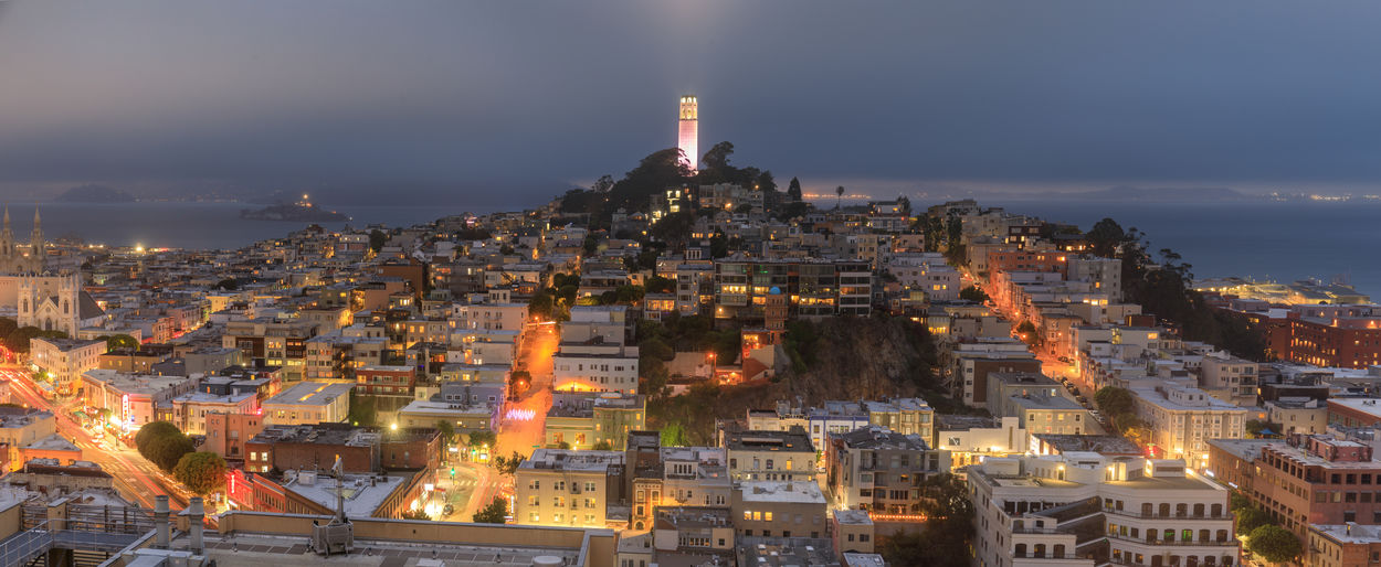 Coit tower lit in pink for sf lgbt pride, with foggy skies over telegraph hill and north beach