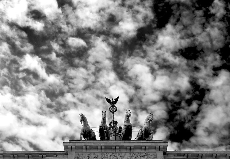 Low angle view of quadriga statue against cloudy sky