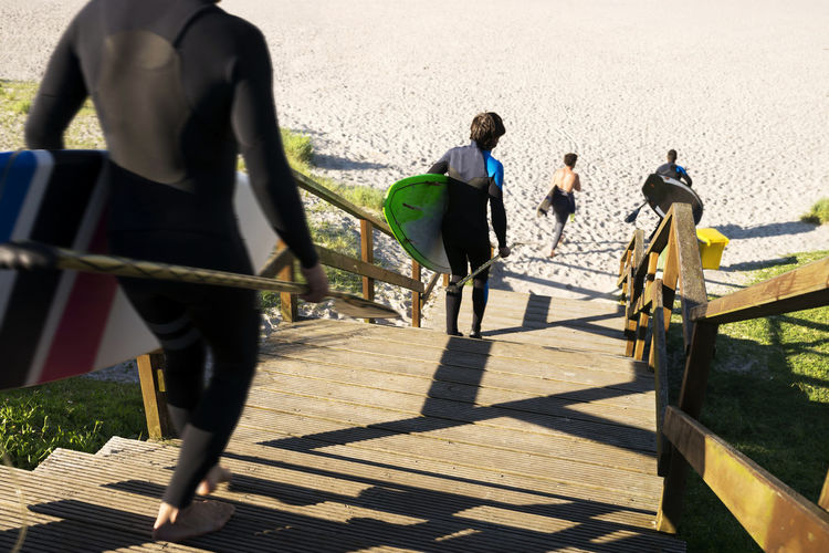 Rear View Of People With Surfboards Moving Down On Steps At Beach