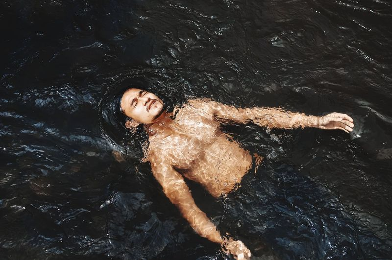 High angle view of woman lying in water
