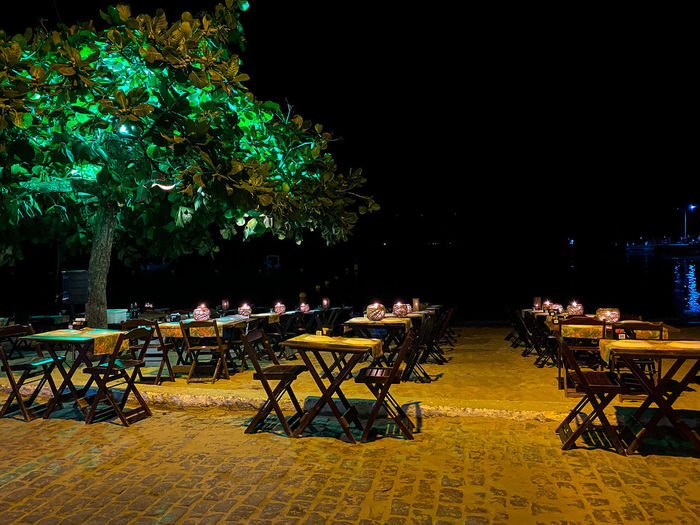 Empty chairs and tables at sidewalk cafe at night