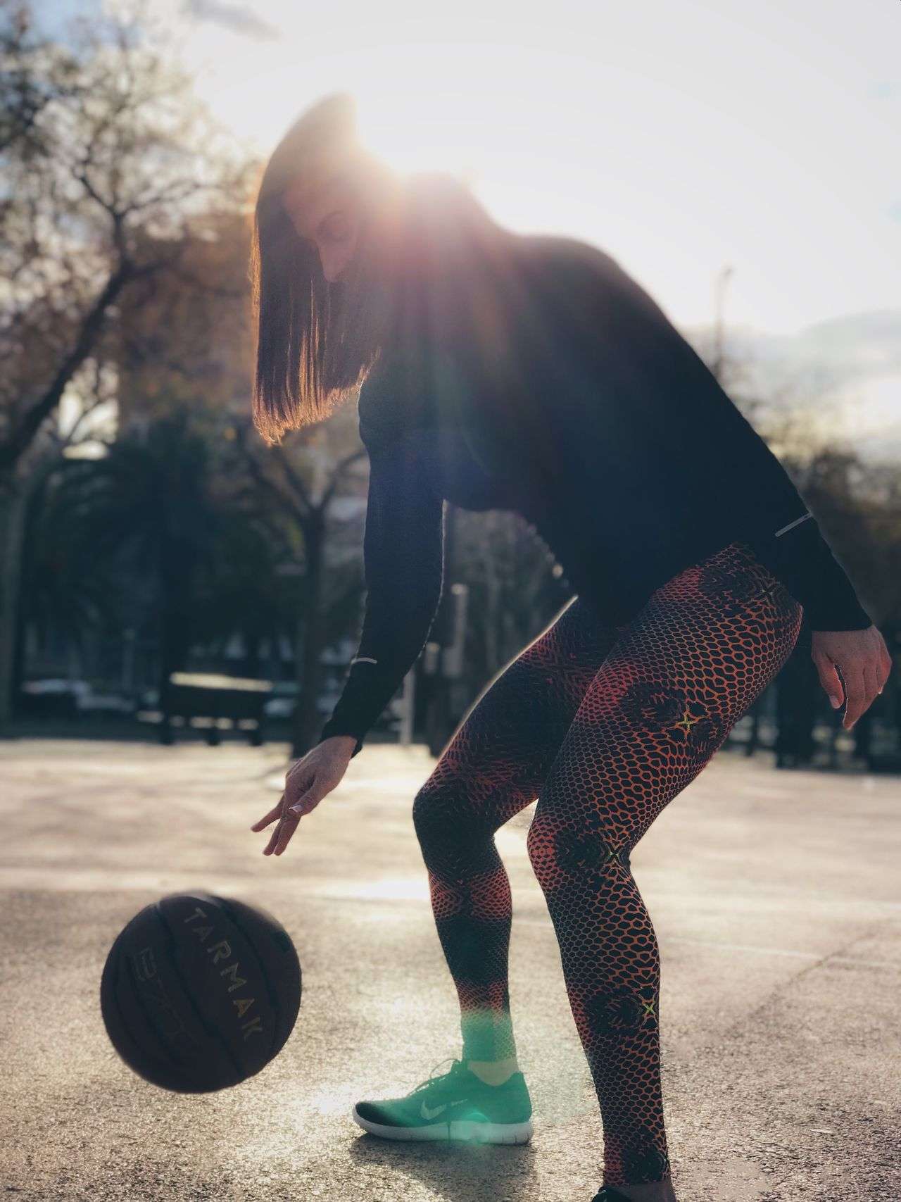 Woman Playing Basketball At Court During Sunny Day