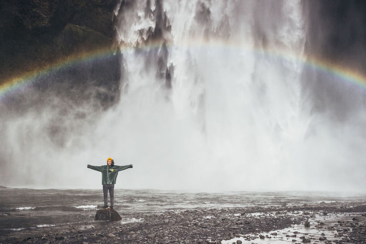 Beauty In Nature Iceland Idyllic Men Motion Nature One Person Outdoors Power In Nature Rainbow Real People Scenics Standing Travel Water Waterfall Market Bestsellers 2017