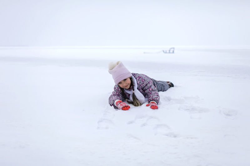 Portrait of cute girl lying down on snow during winter