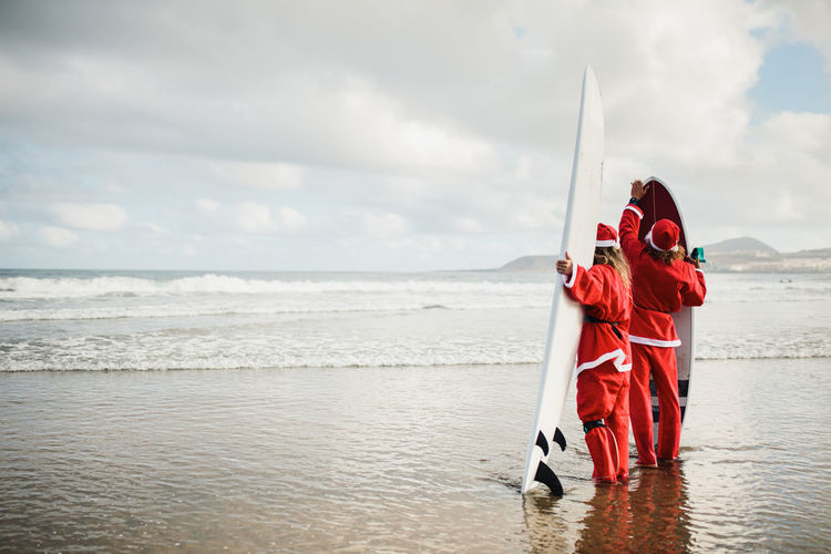 Couple wearing santa costumes holding surfboards in sea