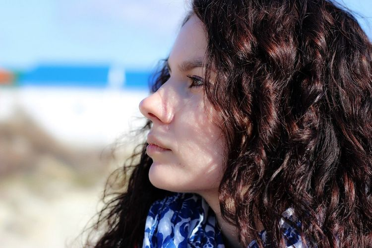 Close-Up Of Thoughtful Woman With Curly Hair Looking Away