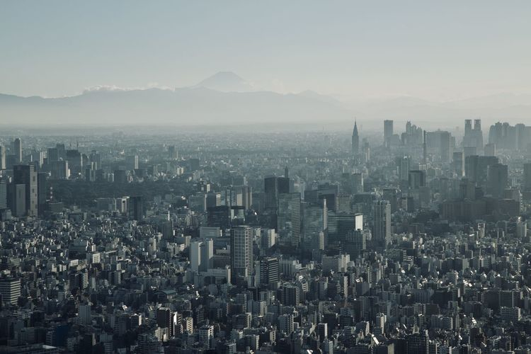 Aerial view of buildings in tokyo against sky