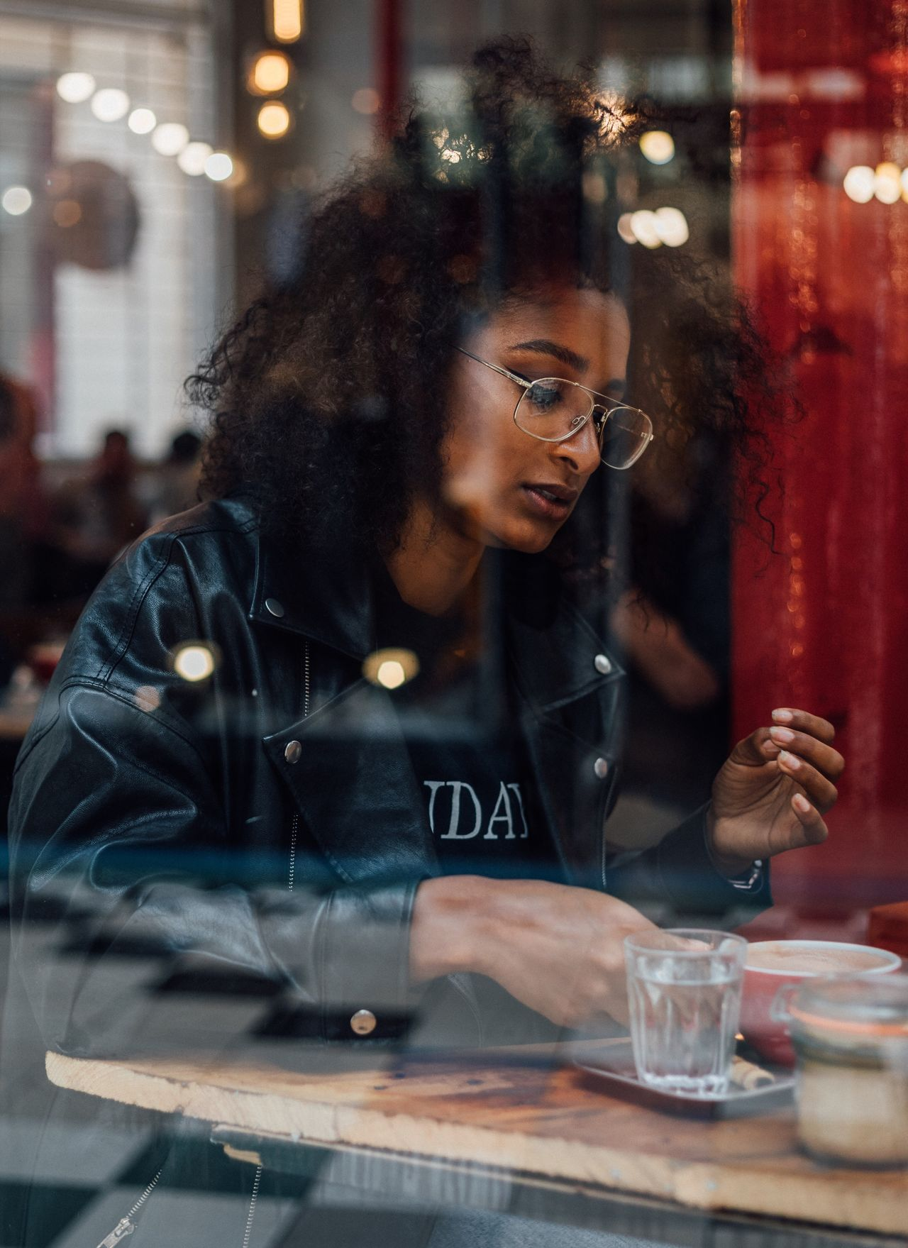 Young woman seen through window at cafe