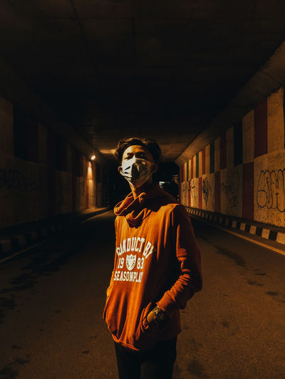 Portrait of young man standing against illuminated wall