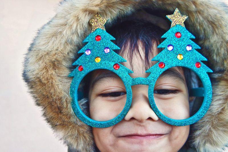 Close-up boy wearing christmas tree glasses