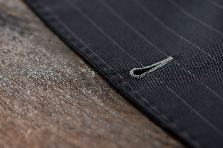 Bespoke jacket. Close up detail of button hold stitching for custom made jacket on old wooden table, professional tailor concept. Art And Craft Bespoketailoring Business Business Suit Close-up Clothing Craft Datails High Angle View Indoors  Industry Jacket Leather Man Made Man Made Object No People Selective Focus Still Life Table Textile Textile Industry Textured  Thread Wood - Material