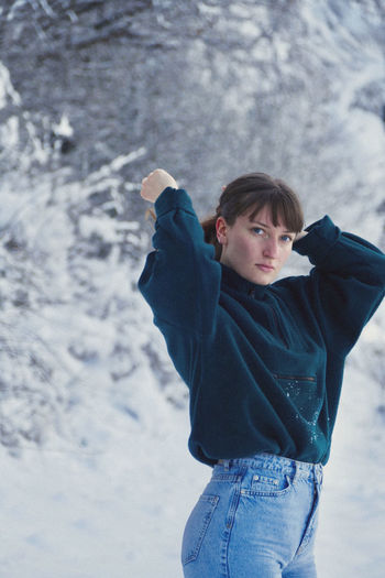 Portrait of young beautiful woman, waist up, standing in snow