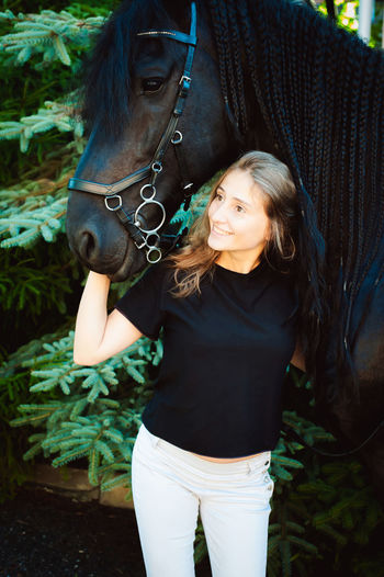 Young woman smiling while standing with horse
