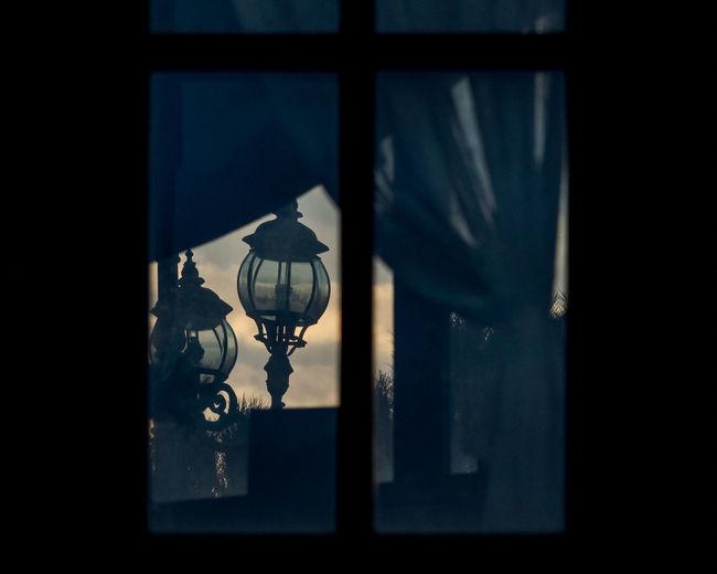 Close-up of light bulb hanging on window