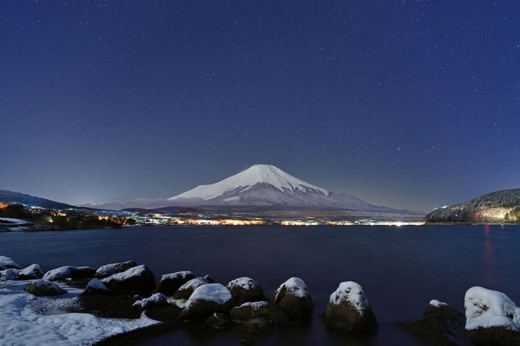 Scenic view of snowcapped mountains against blue sky at night
