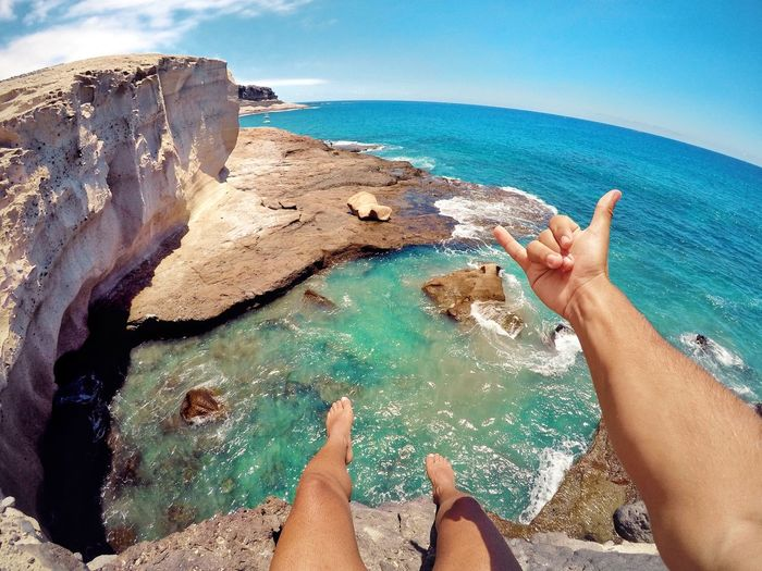 Low section of man gesturing shaka sign on cliff against sea
