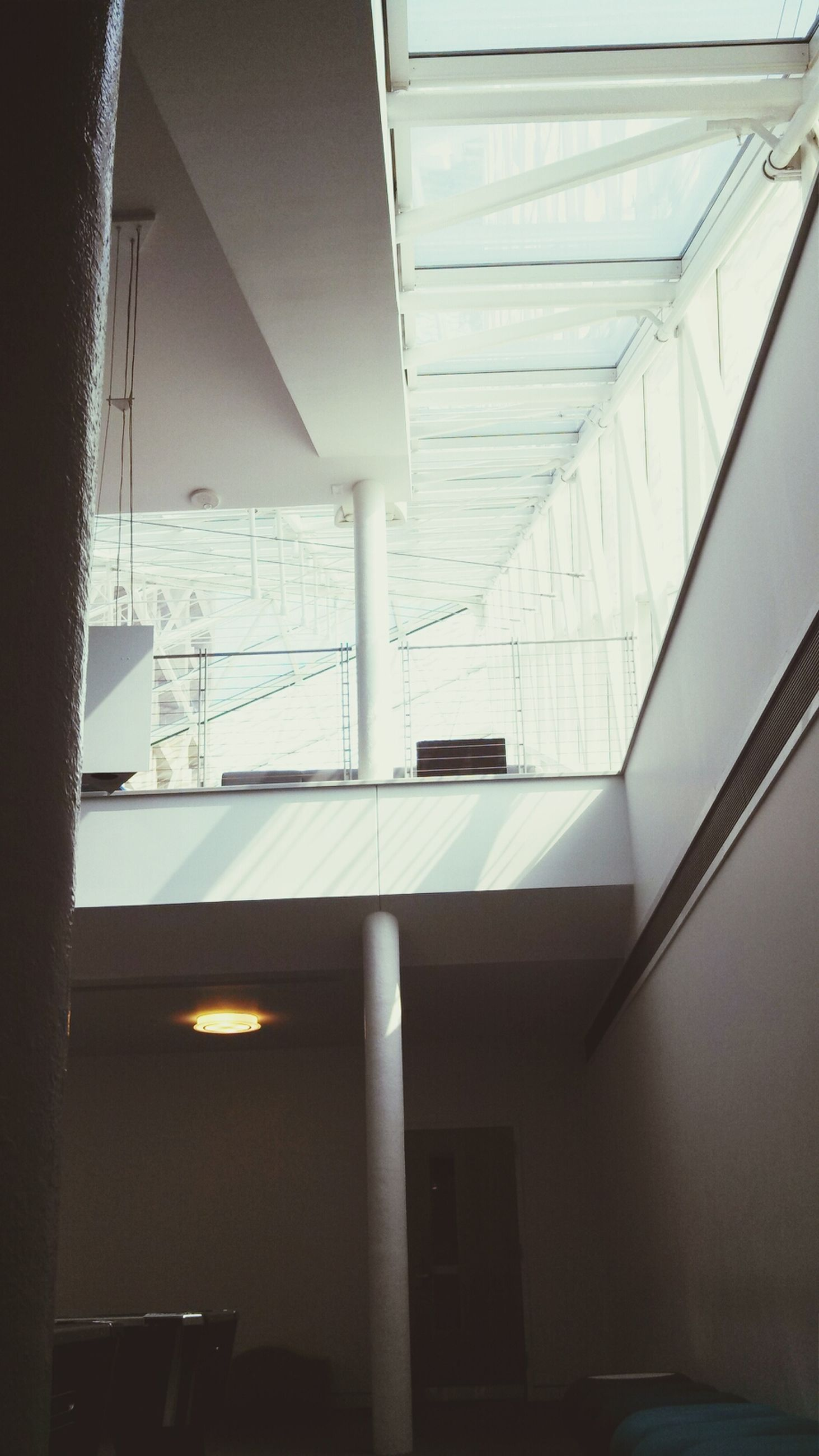 indoors, architecture, built structure, window, low angle view, ceiling, glass - material, building, modern, building exterior, railing, transparent, no people, day, sunlight, transportation, reflection, balcony, skylight, sky
