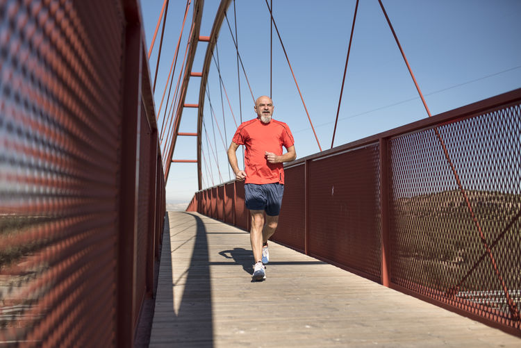 Mature man running on bridge