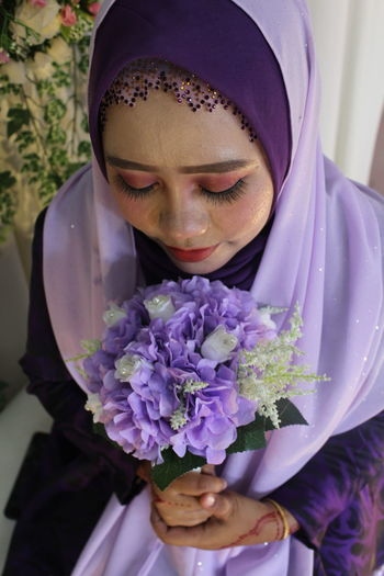High Angle View Of Bride Wearing Wedding Dress While Holding Bouquet