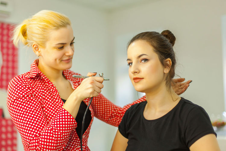Beautician applying hair dye with airbrush to customer in beauty spa